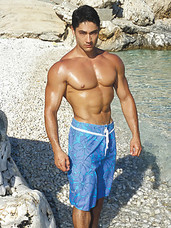 Muscular Julien Salieri poses nude by the ocean as his muscles glisten in the sun
