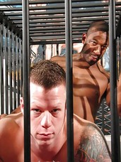Beefy muscle jock Travis Turner and super hot, tattooed black stud, Kamrun, are locked up and naked in a cage. When Travis escapes, however, Kamrun is left inside and Travis has the trapped black man suck his white cock and eat his beefy muscle ass. Travi
