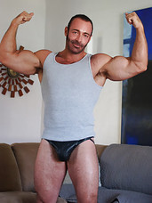 Brad Kalvo is a sexy muscle bear who enjoys showing off his terrific body. And with a body like his, who wouldn't want to show it off? As voyeurs, that coy smile, furry body, and delicious cock definitely makes us want to watch and do a hell of a lot mo